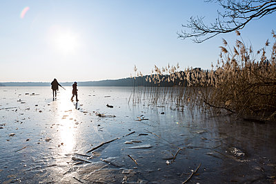 Germany, Brandenburg, Lake Straussee, frozen lake and silhouettes of two people walking on ice - p300m1580728 by Julia Otto