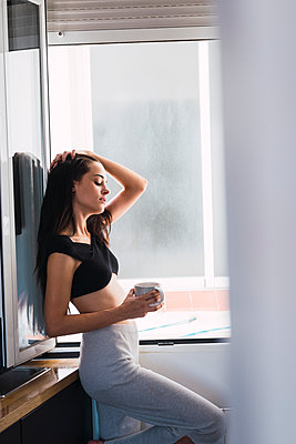 Beautiful young woman with cup of coffee at the window at home - p300m2042251 von Kike Arnaiz
