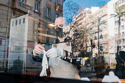 Man wearing protective gloves seen through glass in restaurant - p300m2274992 by Ezequiel Giménez