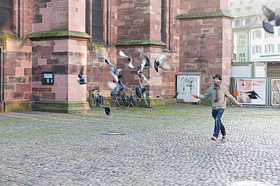 Young man running behind pigeon - p300m884976f by Stefan Rupp