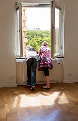 Boy and girl looking through window - p312m1192834 by Susanne Kronholm