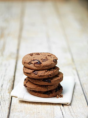 Stack of black forest cookies on tea towel - p429m1095372f by Diana Miller