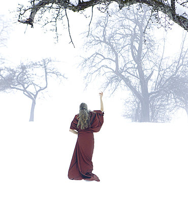 Woman in the snow with a red robe - p5020240 by Tomas Adel
