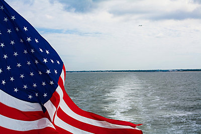 USA flag flying on back of boat - p924m665144 by Mallon Industries