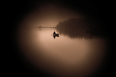Fisherman in his boat on the lake at dawn - p945m2177753 by aurelia frey