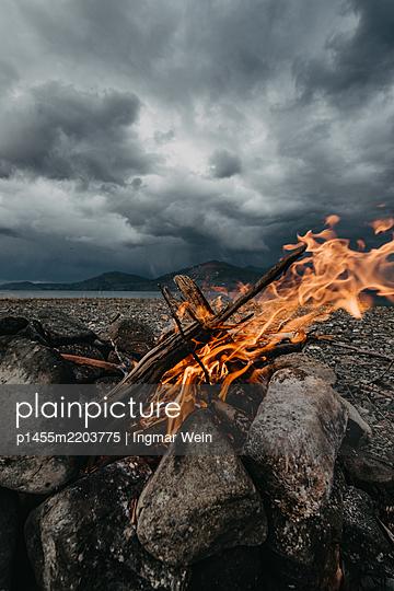 Feuer an einem Steinstrand - p1455m2203775 von Ingmar Wein