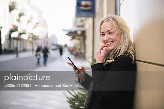 Portrait of smiling young woman with cell phone in the city - p300m2102391 by Hernandez and Sorokina