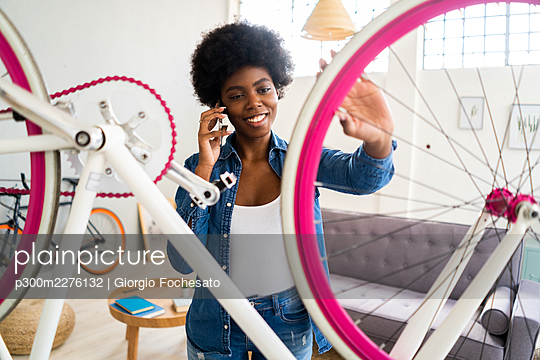 Smiling young woman talking on mobile phone while repairing bicycle at home - p300m2276132 by Giorgio Fochesato