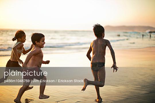 Children running on a beach at sunset - p456m1048759 by Jim Erickson / Erickson Stock