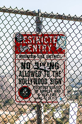 Warning sign behind chainlink fence against sky - p1094m1015301 by Patrick Strattner