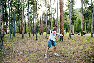 Portrait of boy throwing plastic disc while standing against trees in forest - p1166m2034971 by Cavan Images