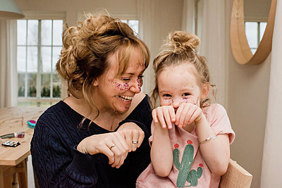 mother and daughter pulling silly faces whilst playing at home - p1166m2165843 by Cavan Images