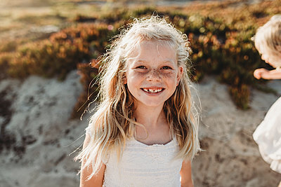 Portrait of young school age girl with freckles smiling at camera - p1166m2165874 by Cavan Images
