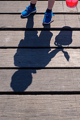 Shadow of a boy holding a bucket at the seaside - p1228m2013352 by Benjamin Harte