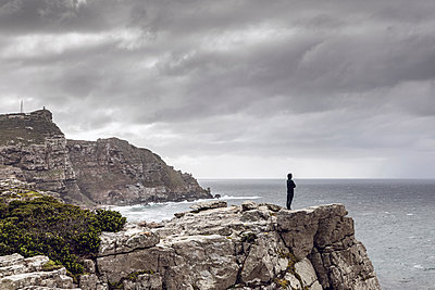Man standing on rocky cliff looking at horizon, Cape Point, Western Cape, South Africa - p300m2155567 by Maya Claussen
