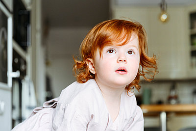 Innocent redhead girl looking away in kitchen at home - p300m2277709 by Katharina und Ekaterina