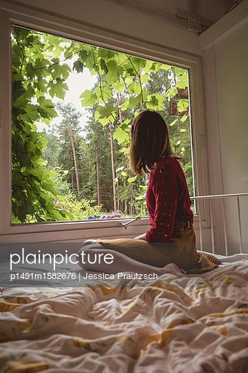 Frau blickt aus dem Fenster - p1491m1582676 von Jessica Prautzsch