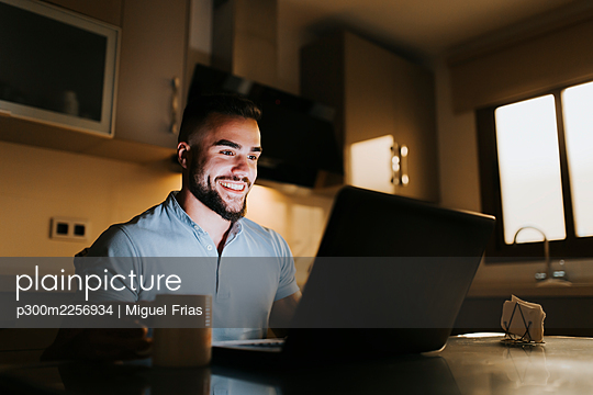 Smiling male entrepreneur working on laptop while sitting at dining table in kitchen - p300m2256934 by Miguel Frias