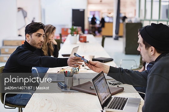 Side view of young man giving smart phone to colleague at desk in office - p426m1407187 by Maskot