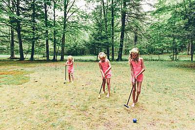 Three girls playing croquet - p1086m2149976 by Carrie Marie Burr