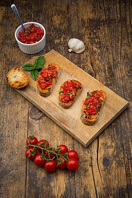 Bruschetta with tomato and basil on wooden board - p300m2012843 von Larissa Veronesi