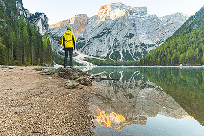 Italy, Braies Lake, man at the lakeside with mountains and forest in background - p300m2081430 von William Perugini
