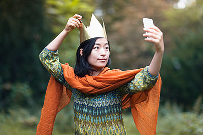 Young woman wearing crown taking selfie through mobile phone while standing at park - p301m1535031 by Ralf Hiemisch