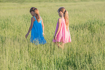 A young girl following her sister; walking through a sunny field - p301m844161f by Vladimir Godnik