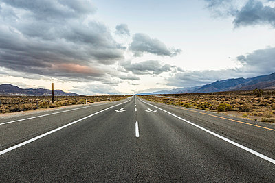 Straight road with direction arrows in Death Valley National Park, California, USA - p429m1469334 by Manuel Sulzer