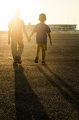 Two brothers walking together holding hands  - p794m924148 by Mohamad Itani