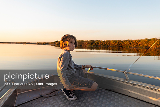 Young boy on a boat on the waters of the Okavango Delta at sunset, Botswana. - p1100m2300978 by Mint Images