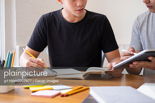Young students campus helps friend catching up and learning. - p1166m2207977 by Cavan Images