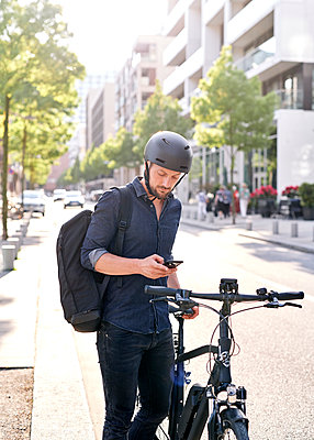 Bicycle courier using smartphone - p1124m2053003 by Willing-Holtz