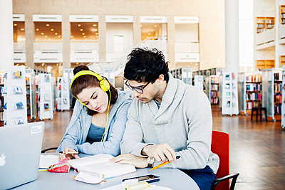 Male and female friends reading book together at table in library - p1185m1027600f by Astrakan