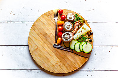 Vegetables on round chopping board, symbol for intermittent  fasting - p300m2013030 von Sandra Roesch