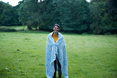 Mid adult woman standing in rural field wrapped in blanket, full length portrait - p429m2023302 by Peter Muller