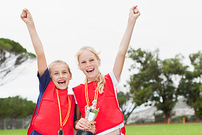 Children cheering with medal - p429m662174f by Hybrid Images