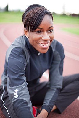 Young female athlete smiling, stretching at track - p4342616f by Alin Dragulin