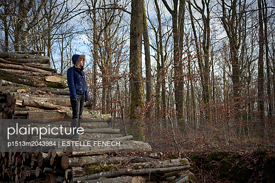 Standing on a pile of tree trunks - p1513m2043984 by ESTELLE FENECH