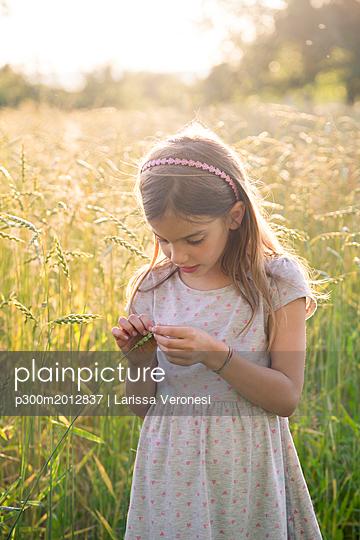 Young girl standing in field at summer evening - p300m2012837 von Larissa Veronesi