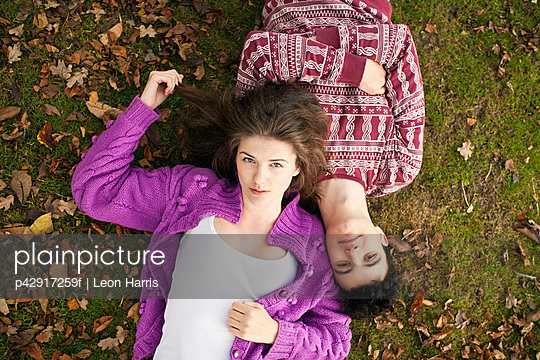 Teenage couple laying in grass in park - p42917259f by Leon Harris