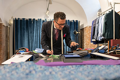 Mature fashion designer choosing fabric and drawing - p1166m2261425 by Cavan Images