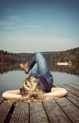 Frau enspannt auf Steg - p1443m1503260 von SIMON SPITZNAGEL