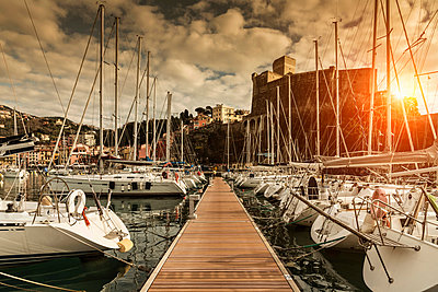 View of waterfront yachts and castle at sunset, Lerici, Liguria, Italy - p429m1418133 by WALTER ZERLA
