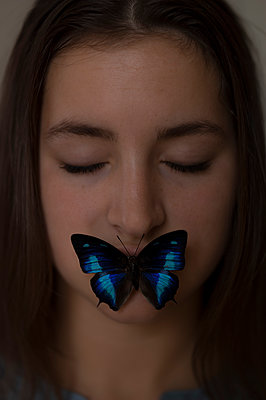 Portrait of woman with butterfly - p552m1538704 by Leander Hopf