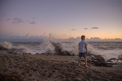 Rear view of boy watching splashing waves at sunrise, Blowing Rocks Preserve, Jupiter Island, Florida, USA - p924m1157702 by Kinzie Riehm