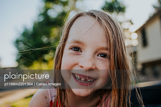 Happy young girl smiling and showing missing tooth - p1166m2201364 by Cavan Images