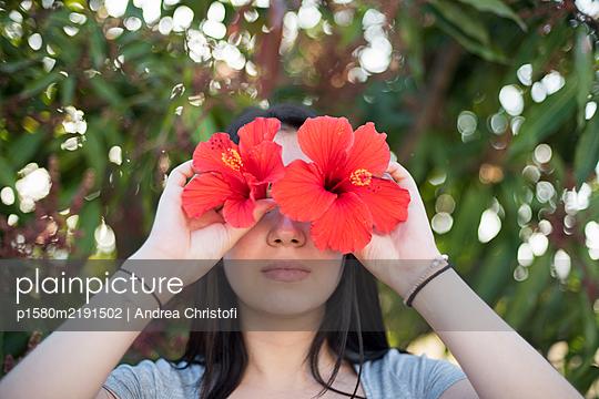 Mädchen mit Hibiskusblüten vor den Augen - p1580m2191502 von Andrea Christofi
