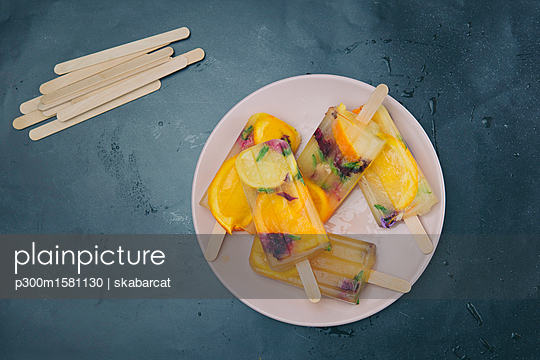 Homemade orange and lemon popsicles with edible flowers on plate - p300m1581130 by skabarcat