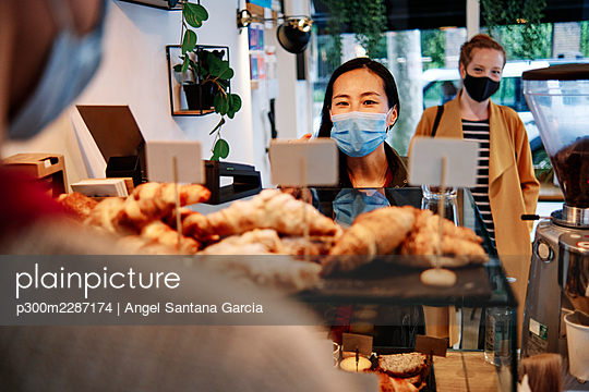 Woman ordering at counter while standing in front of female friend at coffee shop - p300m2287174 by Angel Santana Garcia